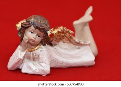 Ceramic angel figurine on a red background
