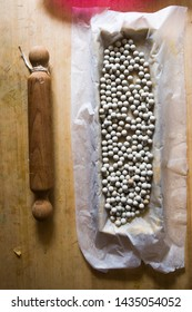 Ceramic baking beans in tart tin,top view, on a wooden board with kitchen roller and ingredients.
