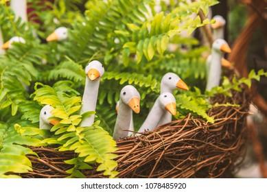 Ceramic birds in fake nest, cute garden decor.