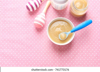 Ceramic bowl with baby food on color background