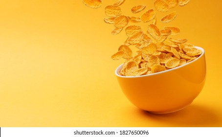 Ceramic bowl of corn flakes. Traditional breakfast cereal. Falling cornflakes on yellow background with copy space