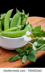 Ceramic bowl of fresh green pea with leaves and white flowers on  wooden cut board, black background
