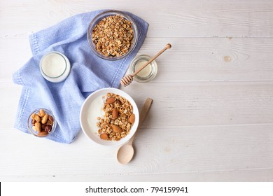 Ceramic bowl of Greek yogurt and mixed nuts. Nutritious vegetarian protein rich diet homemade breakfast with almond milk, cashew, hazelnut, rolled oats on white table. Top view, background, copy space