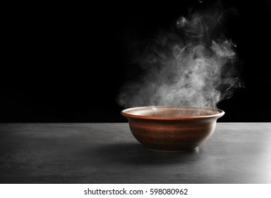 Ceramic bowl with hot liquid on table against dark background