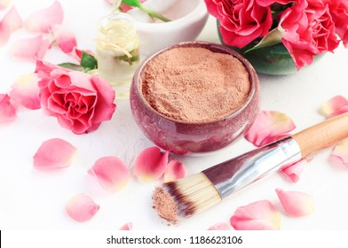 Ceramic bowl of red cosmetic clay for beauty treatment, pink rose petals, aroma oil. Skin care mineral powder mask recipe.