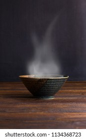 Ceramic bowl with smoke on wooden table.