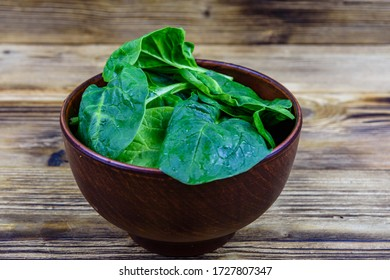 Ceramic bowl with spinach leaves on wooden table