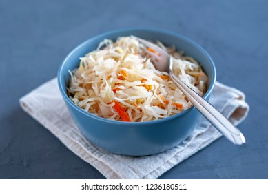 Ceramic bowl of tasty fermented cabbage with fork standing on napkin on wooden tabletop