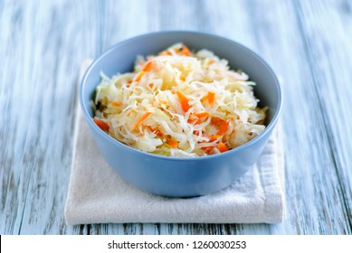 Ceramic bowl of tasty fermented cabbage standing on napkin on wooden tabletop