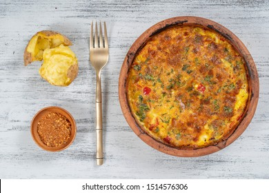 Ceramic bowl with vegetable frittata, simple vegetarian food. Frittata with tomato, pepper, onion and cheese on wooden table, close up. Italian egg omelette, top view
