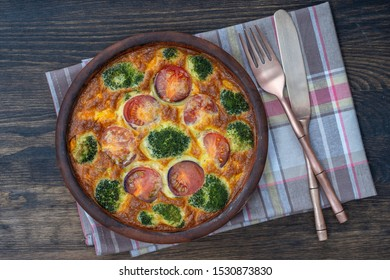 Ceramic bowl with vegetable frittata, simple vegetarian food. Frittata with egg, tomato, pepper, onion, broccoli and cheese on wooden table, close up. Italian egg omelette