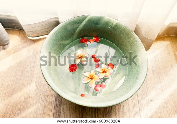 Ceramic bowl with water and flower is for washing or cleaning customer feet, staying near window