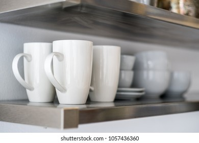 Ceramic bowls and mugs on kitchen shelf