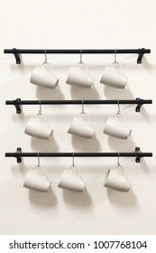 Ceramic coffee cups hanging on hooks in white wall.