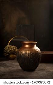 Ceramic copper vase in a dark interior