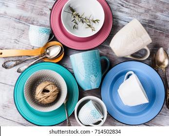 Ceramic crockery tableware on wooden background. Pastel vintage color bowls, dishes, cups