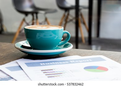 A ceramic cup of coffee on the table with business graph report