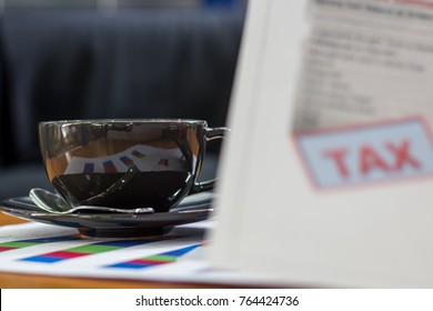 A ceramic cup of coffee with serious  checked TAX document