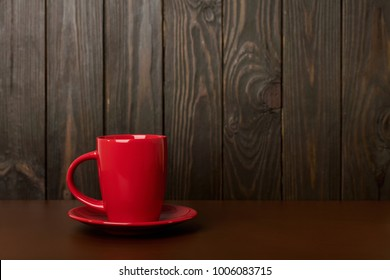 Ceramic cup for coffee and tea of red color on a dark wooden background. Selective focus.