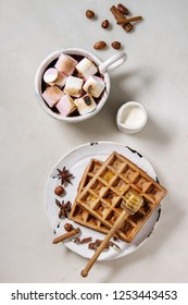 Ceramic cup of hot chocolate with marshmallow s'mores with homemade honey wafers and ingredients above over white marble table. Winter drink. Flat lay, space
