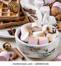 Ceramic cup of hot chocolate with marshmallow s'mores with homemade honey wafers and ingredients above over white marble table. Winter drink. Close up. Square image