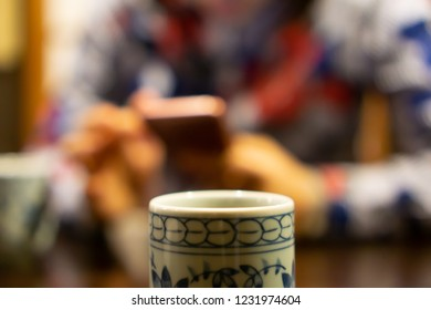 Ceramic cup of Japanese roasted green tea on a table in traditional Japanese restaurant, with young woman using smartphone in the background (This tea looks like Chinese oolong tea)