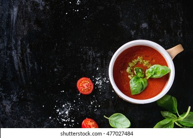 Ceramic cup of tomato gazpacho soup with green pesto sauce, salt and basil over old black iron background with copy space. Top view. Healthy eating concept.