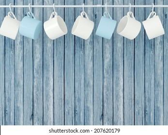 Ceramic cups hanging on hooks in front of wooden blue wall.