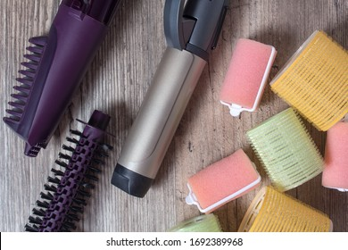 Ceramic Curling iron, hair brush and velcro curlers on a wooden background. Hot styling, boar bristles, hair care. Beauty salon. Curl, wave, volume. Beauty, fashion, style. Hairdresser. Hair roller