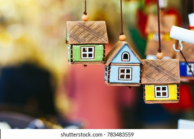 Ceramic decorative handmade toy houses of different colors hang from the roof of the souvenir shop at the Christmas Fair. Space for text