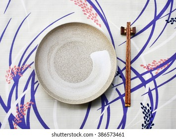 ceramic dish (plate) and chopsticks on table.Flat lay