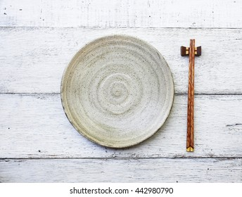 ceramic dish (plate) and chopsticks on white wooden table.Flat lay