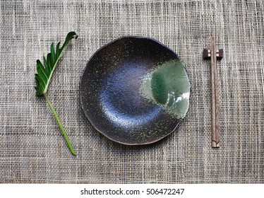 ceramic dish (plate) and chopsticks on bamboo mat.Flat lay