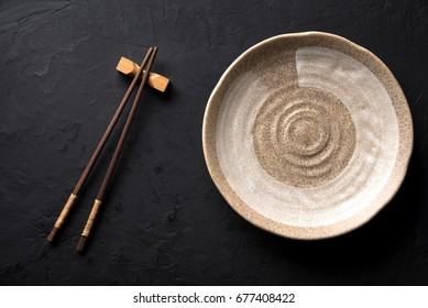 ceramic dish (plate) and chopsticks on dark table