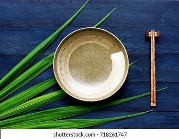 ceramic dish (plate) and chopsticks on blue wooden table.Flat lay