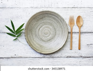Ceramic dish(plate) and wooden spoon,wooden fork on wooden table.Flat lay