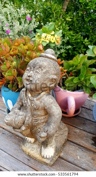 Ceramic doll with wood table and chair in beautiful garden