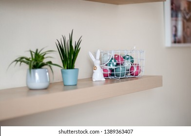 Ceramic Easter Bunny with a golden egg under his arm, multicolored Easter eggs in a white metal basket, indoor plants on the shelf and a photo frame on the wall.