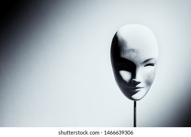 Ceramic female mask on white background with shadows on front