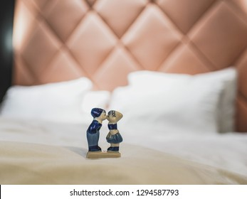 Ceramic figures of a boy and a girl kissing in a hotel room, a place in which someone stays temporarily, close-up, blurred background with copy space