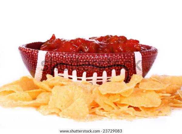 ceramic football dish with salsa in it surrounded by chips