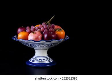 Ceramic fruit bowl with autumn fruits isolated over black background