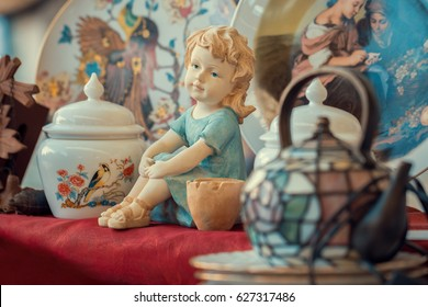 ceramic girl figurine and porcelain vase in sunday flea market. Antique bazaar
