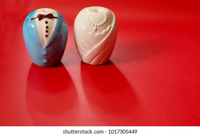 Ceramic grass set of pepper and salt shaker isolated on red background, ceramic couple of groom and bride shape concept for love, valentine's day and married.