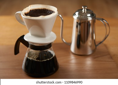 ceramic hand drip coffee brewer (dripper) and drip ground coffee on a glass server with stainless drip pot