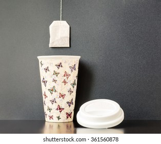 Ceramic insulated cup with colorful butterfly pattern with dark gray background and a tea bag hanging over it.