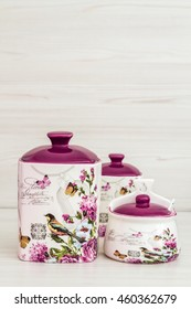 Ceramic jars with flower ornaments and birds on cream wooden background