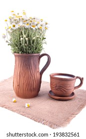 Ceramic jug and cup with milk  standing on the overlay