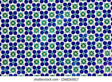 Ceramic mosaic pattern.Colorful floral background. Ceramic mosaic close up. Vietnamese ceramic floor. Dirty floral floor fragment photo. Contrast. Tile