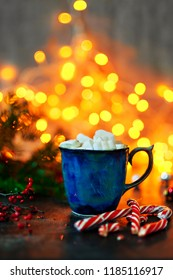Ceramic mug with hot cocoa and marshmallows and candy canes in the background of Christmas lights